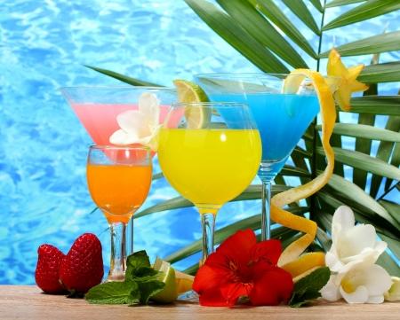 cócteles exóticos y flores en la mesa en el fondo del mar azul