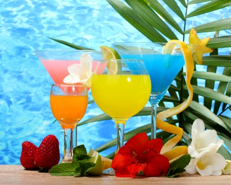 bebidas alcoh�licas: c�cteles ex�ticos y flores en la mesa en el fondo del mar azul Foto de archivo