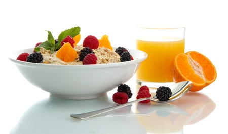 breakfast: tasty oatmeal with berries and glass of juice, isolated on white Stock Photo