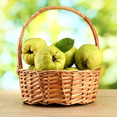 sweet quinces with leaves in basket, on green background Stock Photo - 16246119