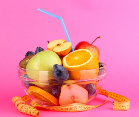Glass bowl with fruit for diet and measuring tape on pink background Stock Photo - 16244506
