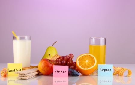 Dietary foods for breakfast, dinner and supper on purple background photo
