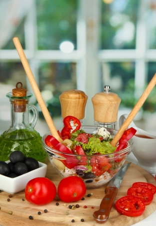 Fresh greek salad in glass bowl surrounded by ingredients for cooking on wooden table on window background Stock Photo - 16246085