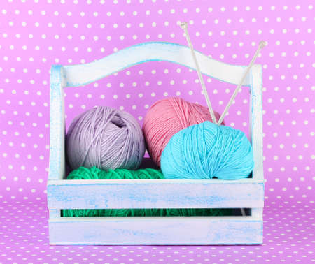 Knitting balls in box on color background photo