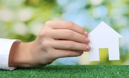 concept: woman hand with paper house on green background, close up Stock Photo - 16244551