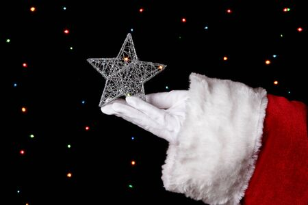 Santa Claus hand holding christmas star on bright background Stock Photo - 16244473