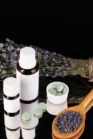 bottles of medicines and herbs on black background. concept of homeopathy Stock Photo - 16277594
