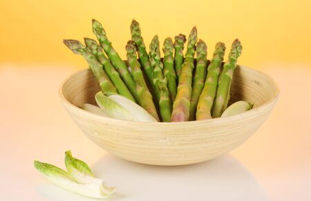 nutritiously: Fresh asparagus in wooden bowl on colorful background  Stock Photo