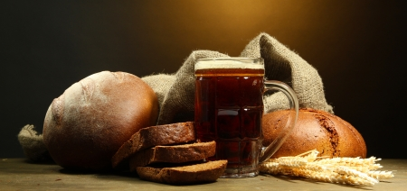 tankard of kvass and rye breads with ears, on wooden table on brown background Stock Photo - 16291869