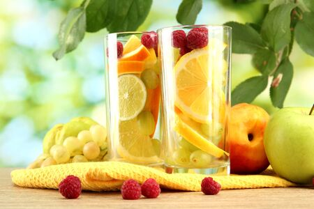 glasses citrus fruits and raspberries, on green background photo