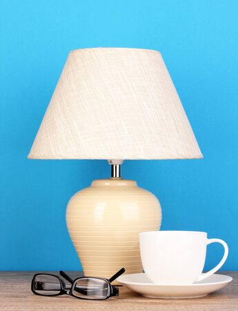 table lamp with cup and glasses on blue background Stock Photo - 16279707