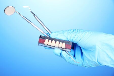 Hand in blue glove holding dental tools and denture on blue background photo