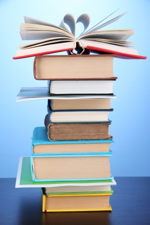 Stack of interesting books and magazines on wooden table on blue background photo