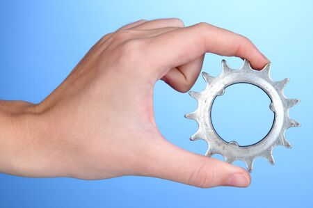 Man holding metallic cogwheel in his hand on blue background Stock Photo - 16278660