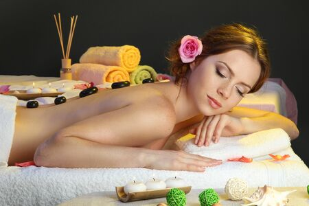 beautiful young woman in spa salon with spa stones photo