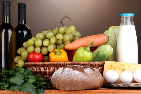 alimentacion equilibrada: Composici�n con verduras en la cesta de mimbre sobre fondo marr�n Foto de archivo