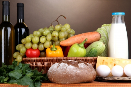 balanced diet: Composition with vegetables  in wicker basket on brown background