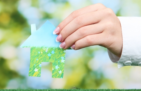 concept: woman hand with paper house on green background, close up Stock Photo - 16278142