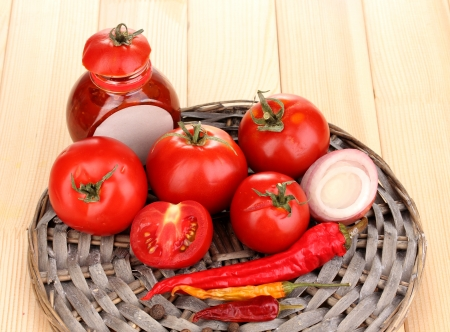 Ketchup and ripe tomatoes on wooden table Stock Photo - 16292080