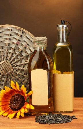 oil in bottles, sunflower and seeds, on wooden table on brown background photo