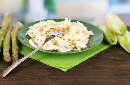 nutritiously: Plate with coleslaw, asparagus and chicory on wooden table on room background Stock Photo
