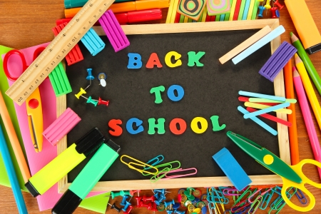 Small chalkboard with school supplies on wooden background. Back to School Stock Photo - 16295161