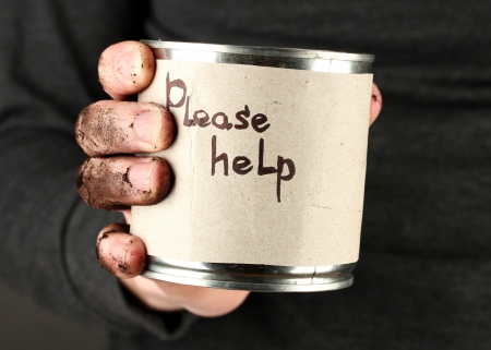 waster: homeless man asks for help, on black background close-up Stock Photo