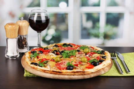 Delicious pizza with glass of red wine and spices on wooden table on window background photo