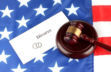 decree: Divorce decree and wooden gavel on american flag background