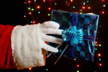 Santa Claus hand holding gift box on bright background Stock Photo - 16283579