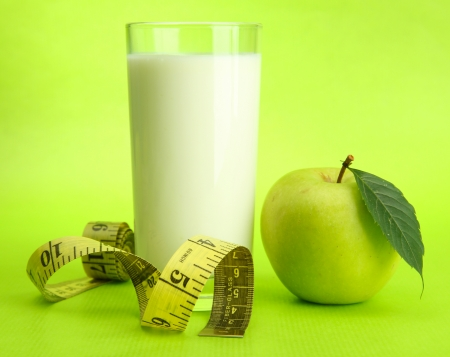 Glass of kefir, apple and measuring tape, on green background photo