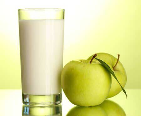 Glass of kefir and apples, on green background photo