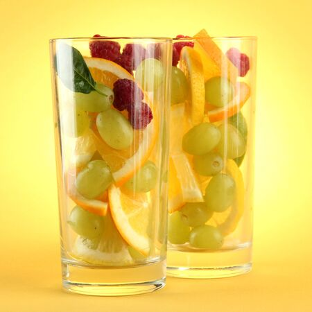 transparent glasses with citrus fruits, on yellow background Stock Photo - 16282979
