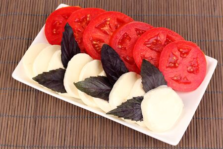 tasty mozzarella with tomatoes on plate on mat photo