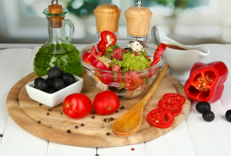 Fresh greek salad in glass bowl surrounded by ingredients for cooking on wooden table on window background Stock Photo - 16283576