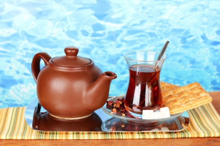 glass of Turkish tea and kettle on color background photo