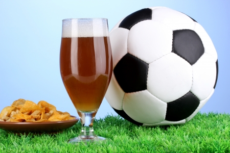 Glass of beer with soccer ball on grass on blue background photo