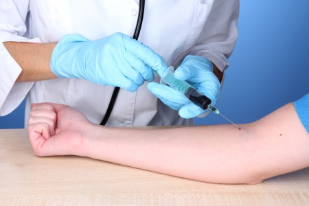 Nurse takes blood from the veins on blue background photo