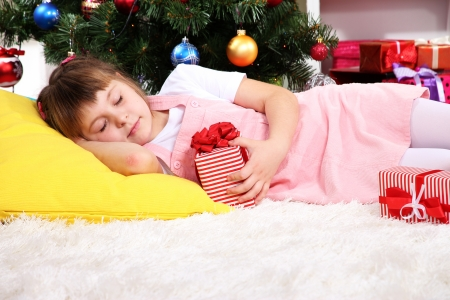 festively: The little girl fell asleep with gift in their hands in festively decorated room Stock Photo