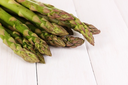 nutritiously: Fresh asparagus on white wooden table background