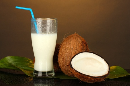 glass of coconut milk and coconuts on brown background close-up photo