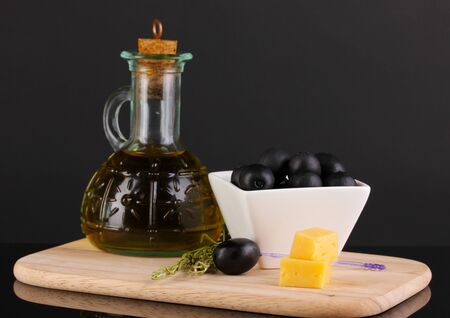 Black olives in white bowl with rosemary,olive oil and cheese on board isolated on black photo