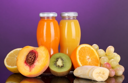 Delicious multifruit juice in a bottle and fruit next to it on purple background photo