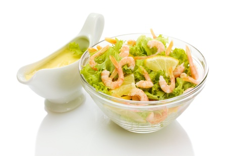 salad with shrimps, lemon and lettuce leaves in bowl and sauce, isolated on white photo