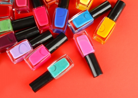 nails: Group of bright nail polishes, on red background