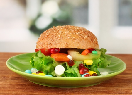 Conceptual image for nutritional care: assorted vitamins and nutritional supplements in bun.On bright background photo