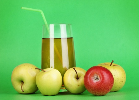 Useful apple juice with apples around on green background photo
