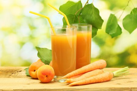 glasses of carrot and  apricot juice on wooden table on green background photo