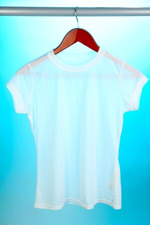 White t-shirt on hanger on blue background photo