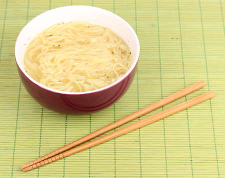 asian noodles in bowl on bamboo mat photo